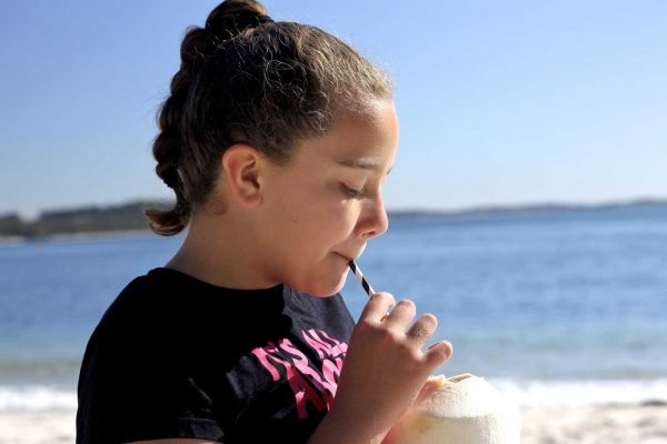 girl drinking coconut on the beach