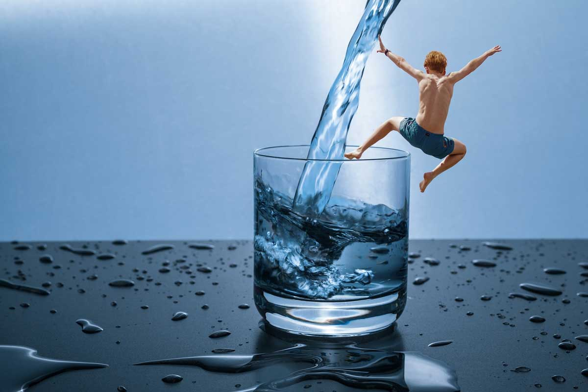 boy jumping in water glass
