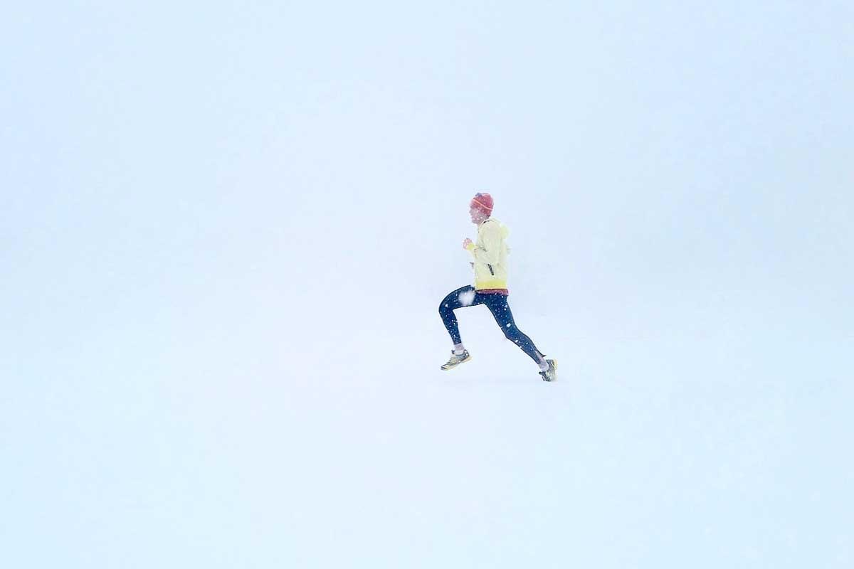 man running in the winter snow