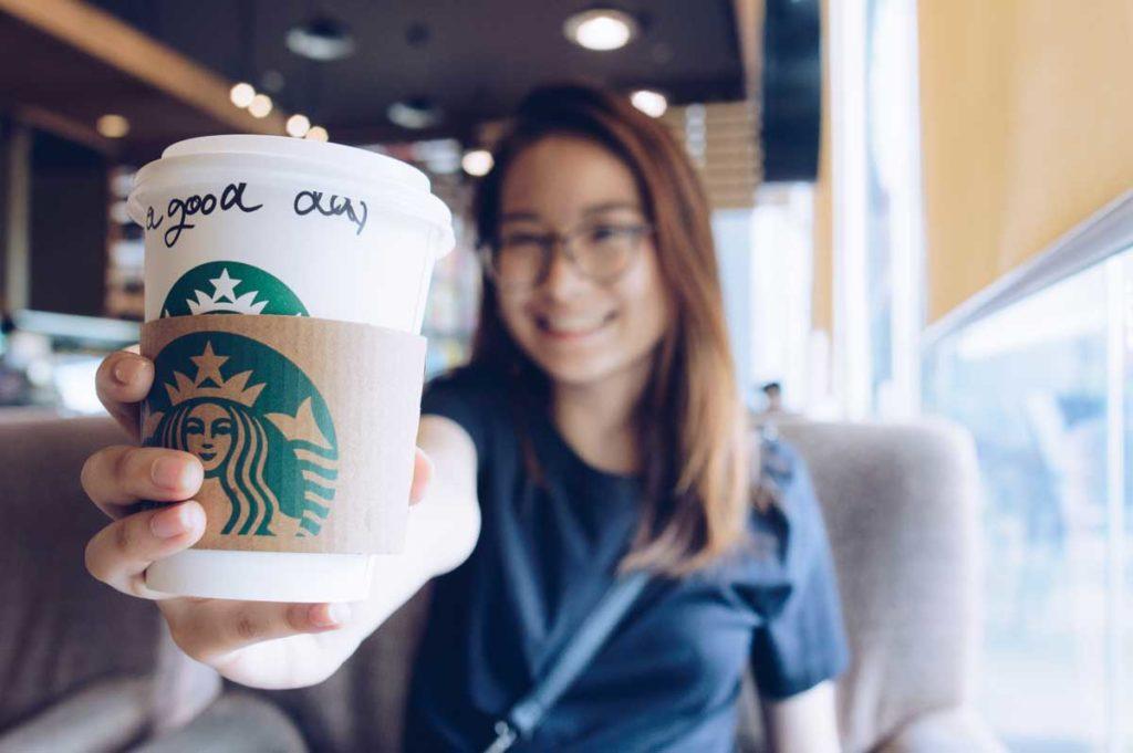 girl holding a starbucks coffee