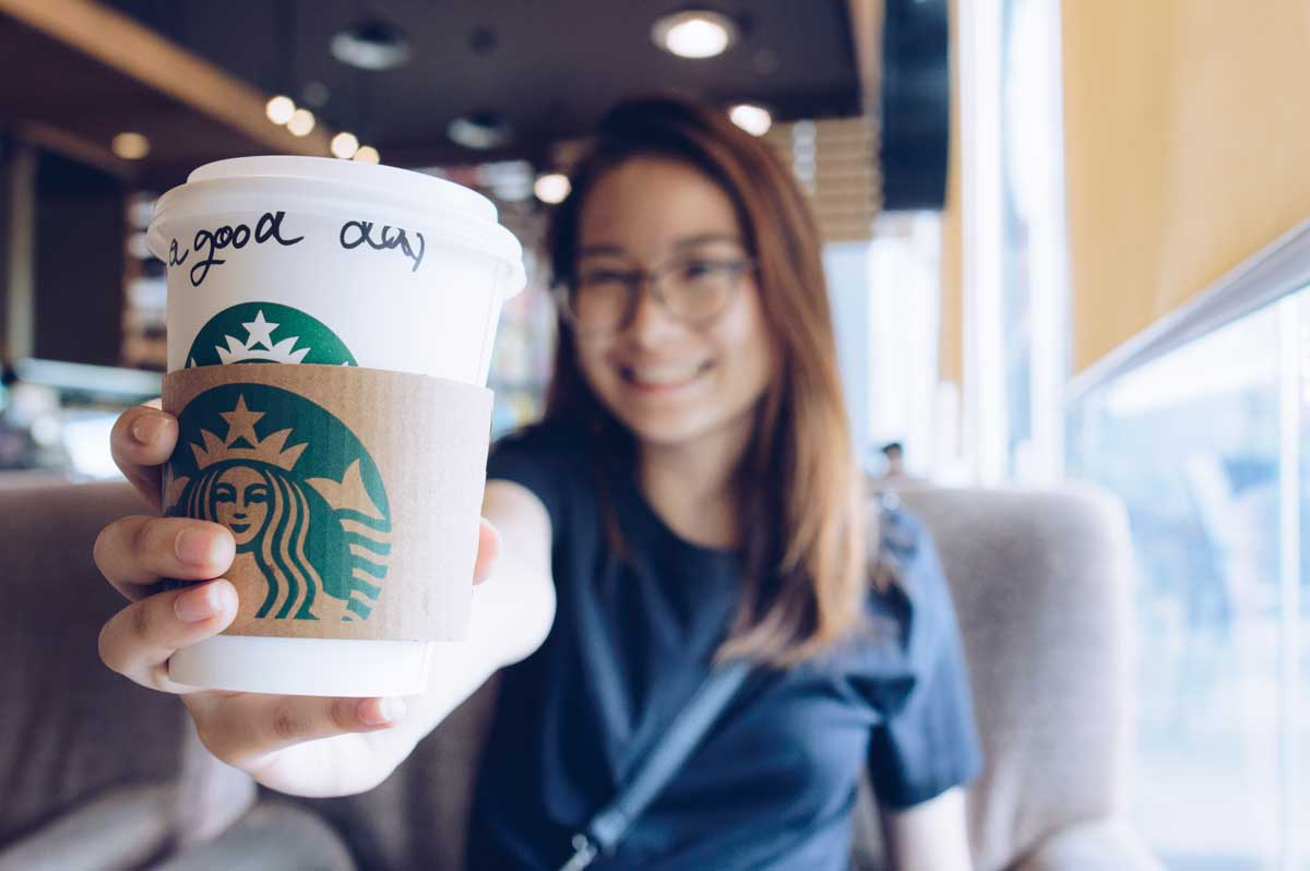 girl holding a starbucks coffee