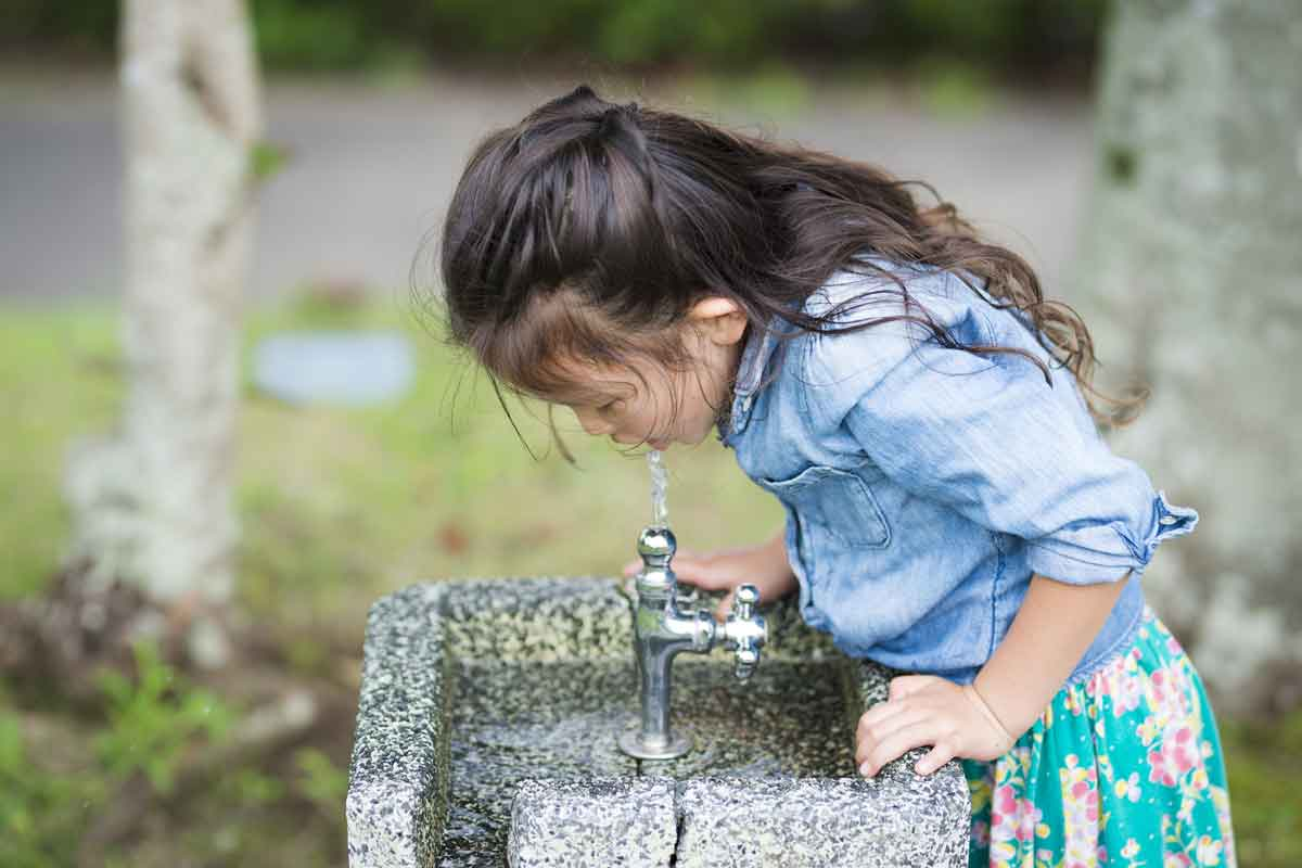 young girl drinking outside tap water