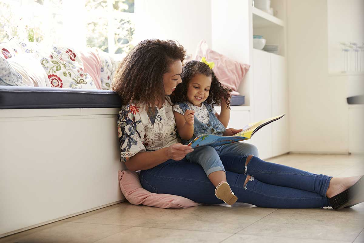 mom reading to her child laughing