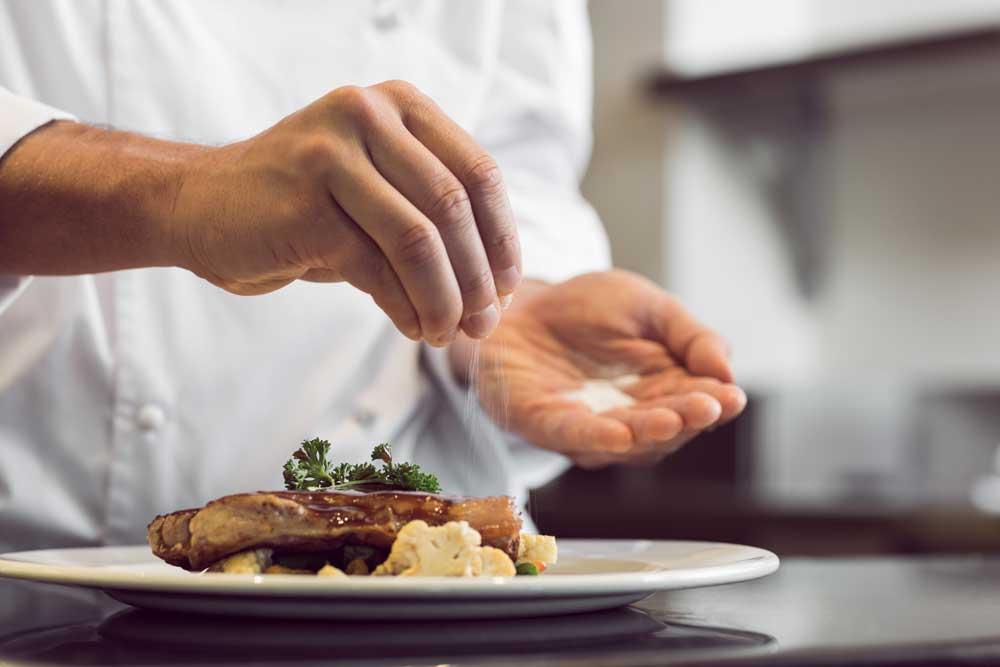 chef puts salt on steak for taste
