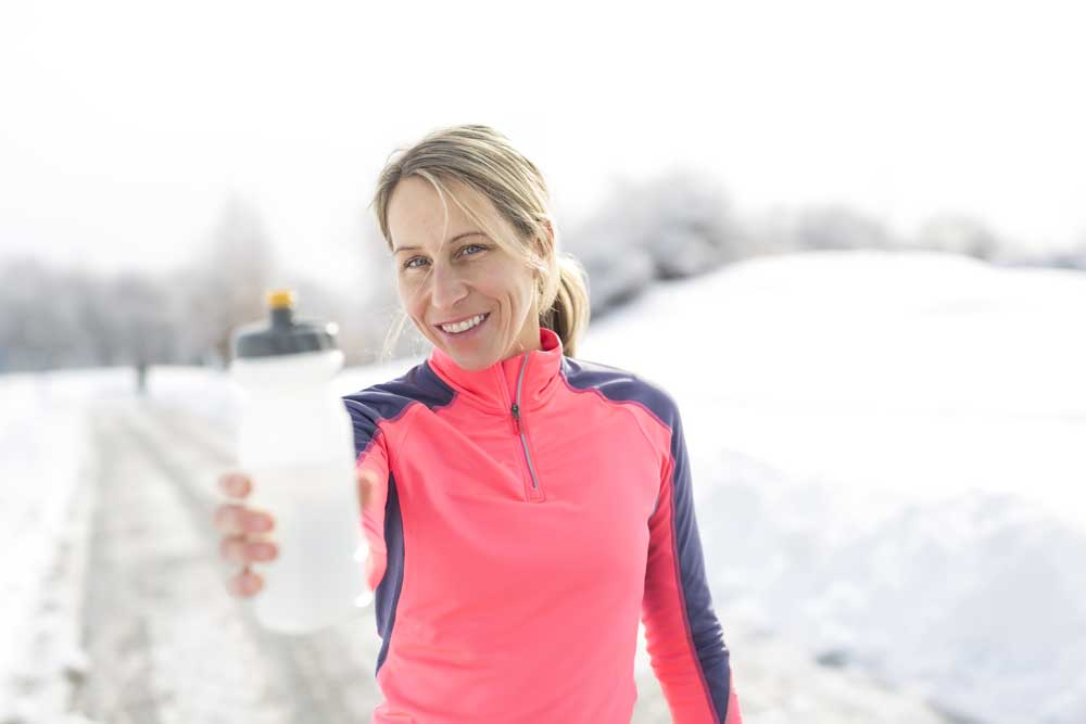woman holding water bottle out in winter
