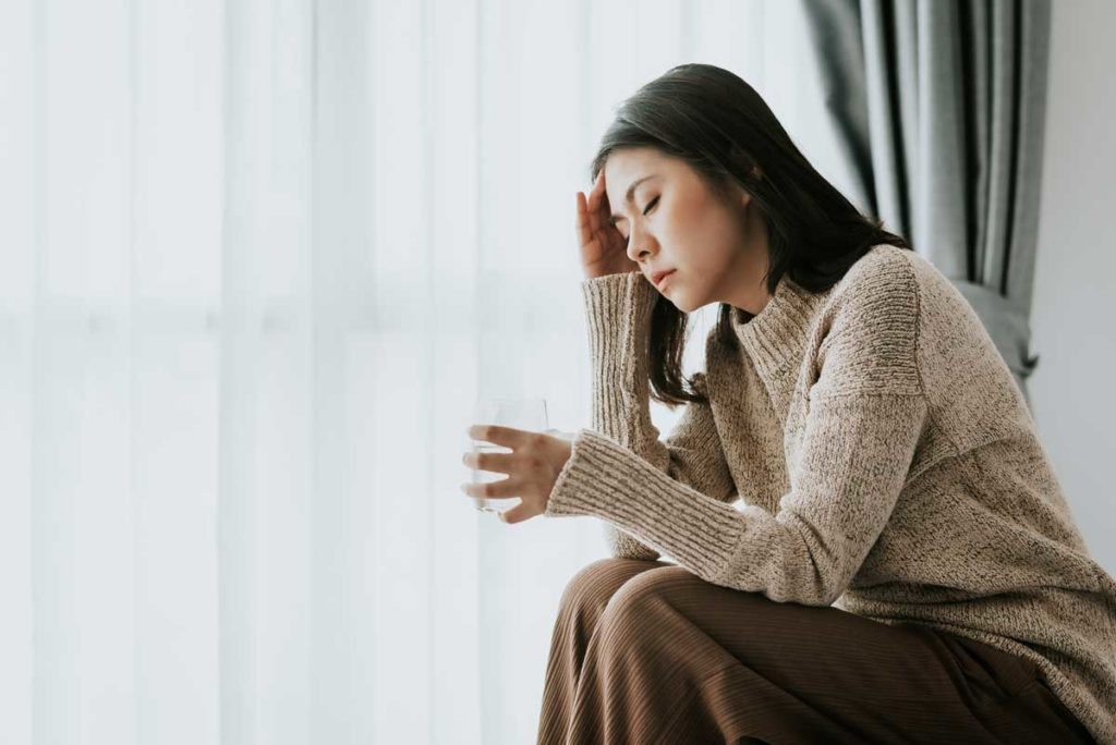 woman sitting on edge of bed with hangover